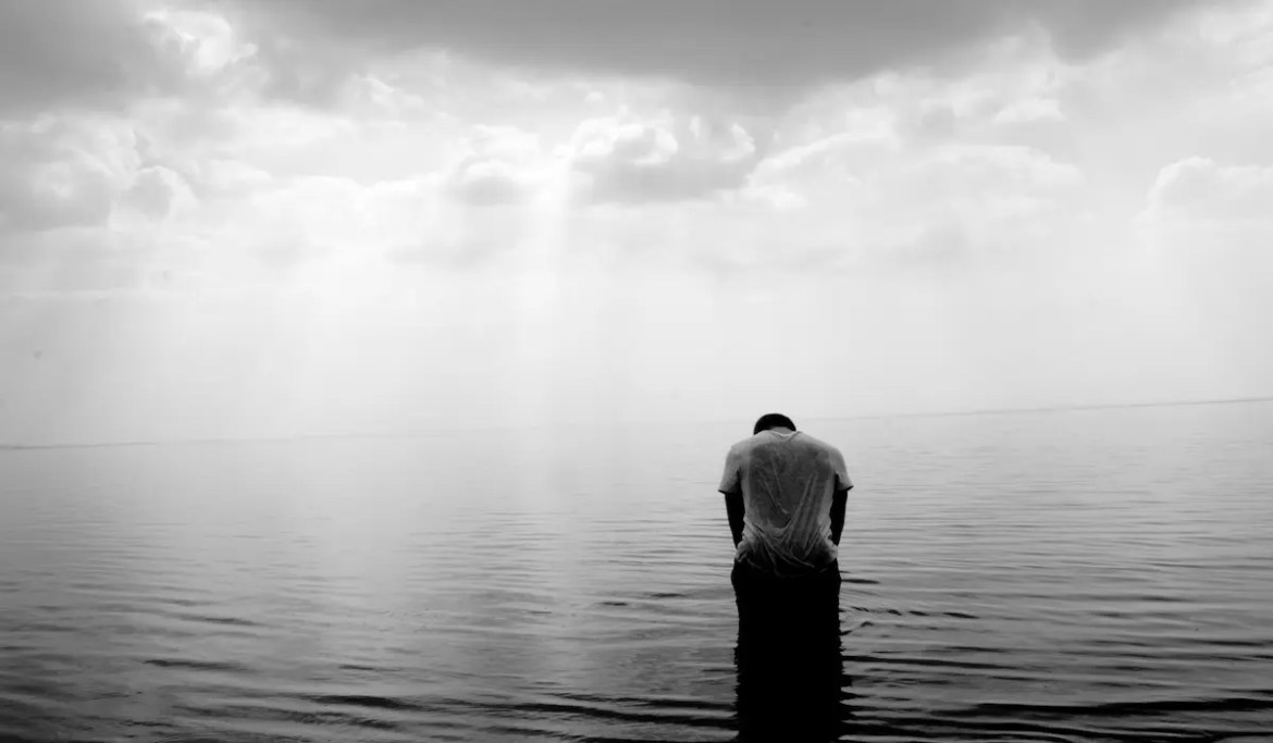 A black and white photo shows a man bending his head in prayer while wading in a lake as the sun shines through the clouds. This picture serves as the featured image of Balanced Achievement's article examining Gratitude.