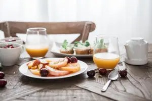 A kitchen table is shown with a pleasant looking breakfast spread of fruits, bread, oatmeal and orange juice. This image represents the idea that we can obtain bountiful benefits from mindful eating.