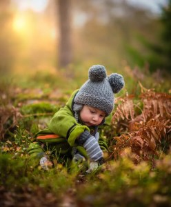 An image shows a child playing in a forest with a snowcap on. This image represents the idea that humans don't validate their own worth because of childhood beliefs.