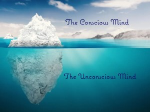 A diagram shows an iceberg with 1/3rd of it above water and 2/3rd submerged. On the image is written the conscious (above the water) and unconscious mind (below the water). Sigmund Freud came to believe the inner workings of the human mind operate partly conscious and partly unconscious.