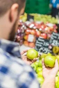 An image shows the side of a man as he is comparing two different green apples in a grocery store. This image represents the idea of nurturing our mindful eating practice.