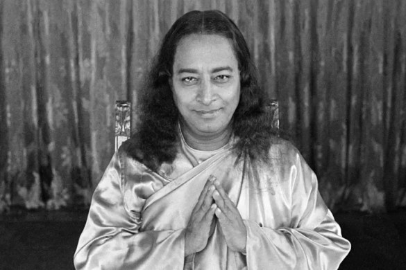 An image shows the great Hindu sage Paramahansa Yogananda slightly smiling with his hands in a namaste greeting/prayer posture.