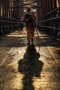 A Hindu Sadhu, or spiritual seeker, is shown walking on a bridge with his shadow in front of him. This image represents the idea that inside each of us is two different parts: The ego and the true self or silent witness within.