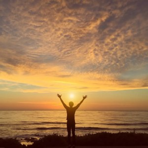 An image shows a silhouette of a man standing on the shore of an ocean. His hands are raised in a celebratory position as the sun is shining down on him. This image represents the idea that we can make the game of real life truly winnable.