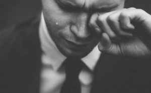 An image shows a man wiping one of his eyes as a tear comes down the other one. This image represents the idea that our core beliefs determine our self-esteem which in turn determines our levels of subjective well-being.