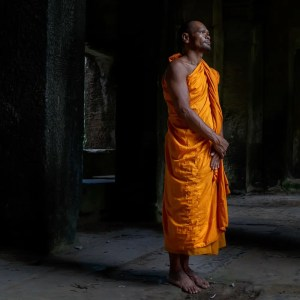 An image shows a Thai Buddhist monk as he is standing stoically.