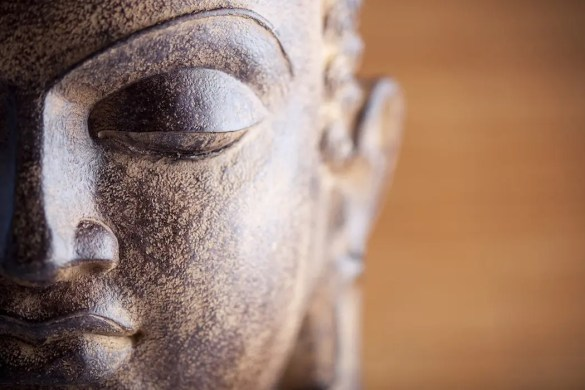 An image shows a close up of a brown wooden Buddha statue. This pictures serves as the featured image of Balanced Achievement's article on The teachings of the Buddha and the Four Noble Truths.