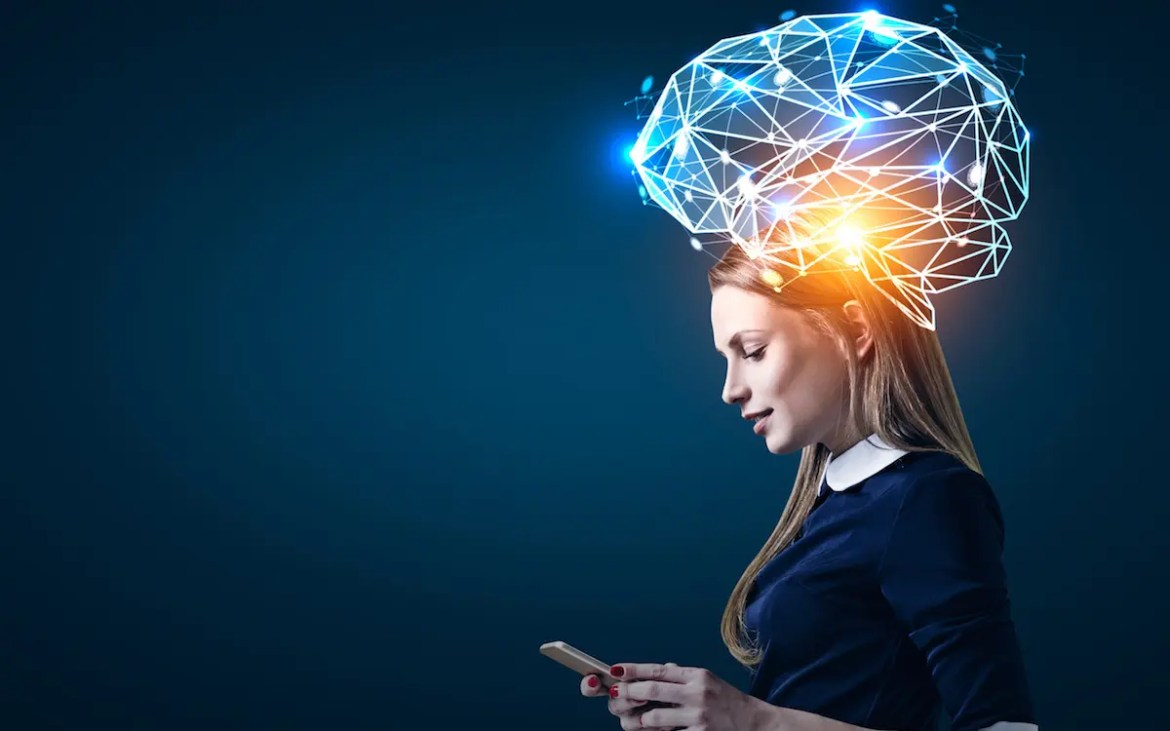 An image shows the side view of a blond businesswoman looking at her smartphone with a is a large blue brain hologram around her head. This picture serves as the featured image for Balanced Achievement's article on Lumosity Mobile.