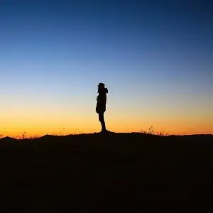 An image shows the silhouette standing on a hill as a dramatic orange and blue sunrise is taking place behind him.
