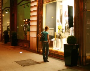 An image shows a woman looking into a clothing store window at night.