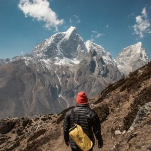 An image shows the back of a man in the mountains as he is looking at a immense mountain summit which dwarfs him in comparison.