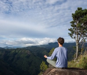 An image shows a man meditating in the mountains. The image shows the back of him as he is facing an expansive mountains terrane.