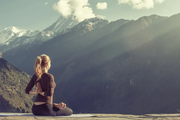 A woman is shown high in the mountains practicing meditation and the sun shines down on her. This picture serves and the featured image for balanced achievement article on meditation for success.