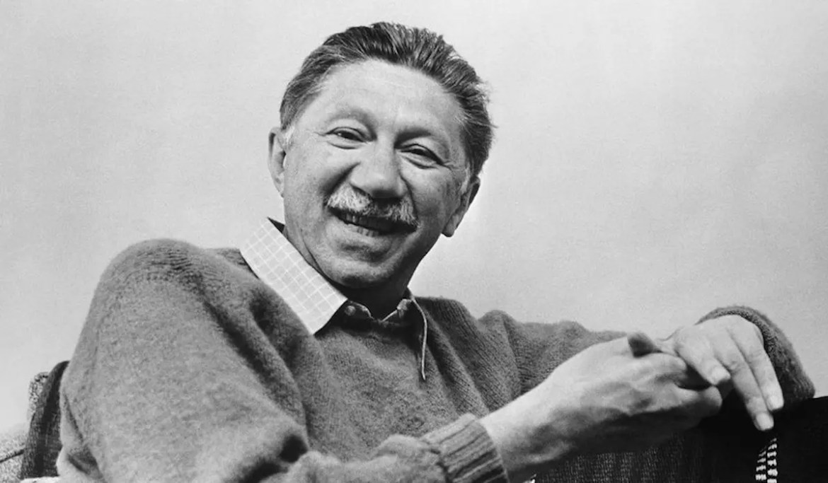 An image shows Abraham Maslow sitting in a chair smiling from ear to ear.