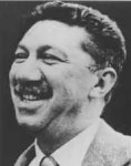 A headshot of Abraham Maslow shows the iconic psychologist happily smiling.