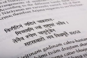 An image shows a close-up of text from the Bhagavad Gita. This image is featured in Balanced Achievement's article on karma and dharma.