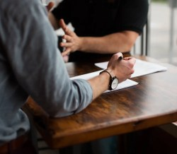 An image shows the torso of a man who's holding a pen in his hand, looking as if he's going to write, while he is talking to another individual. This image represents the idea that we can gain valuable feedback by asking questions of others.