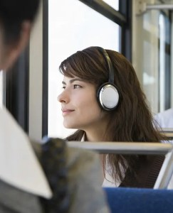 An image shows a young woman commuting on a train with headphones on as she looks out the window with a slight smile on her face. This image represents the idea that personal development podcasts can transform our lives.