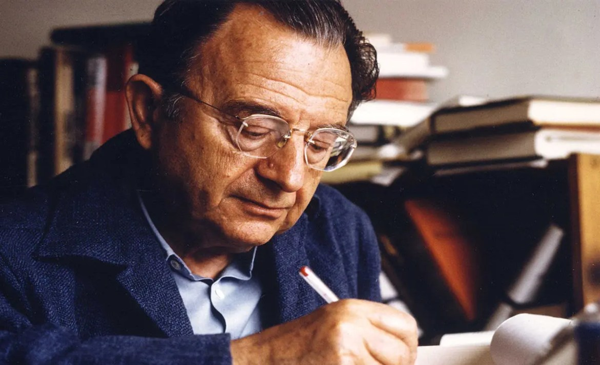 An image shows German social psychologist Erich Fromm writing. This picture serves as the featured image for Balanced Achievement's article looking at 20 Erich Fromm quotes.