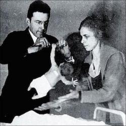An image shows psychologists John B. Watson preforming a reflex test on a baby. Watson was one of the most influential psychologists of the Behavioral movement in the early parts of the 20th century.