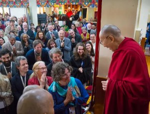 An image shows His Holiness the 14th Dalai Lama arriving, to much fanfare, for day two of the 2018 Mind and Life Dialogue.