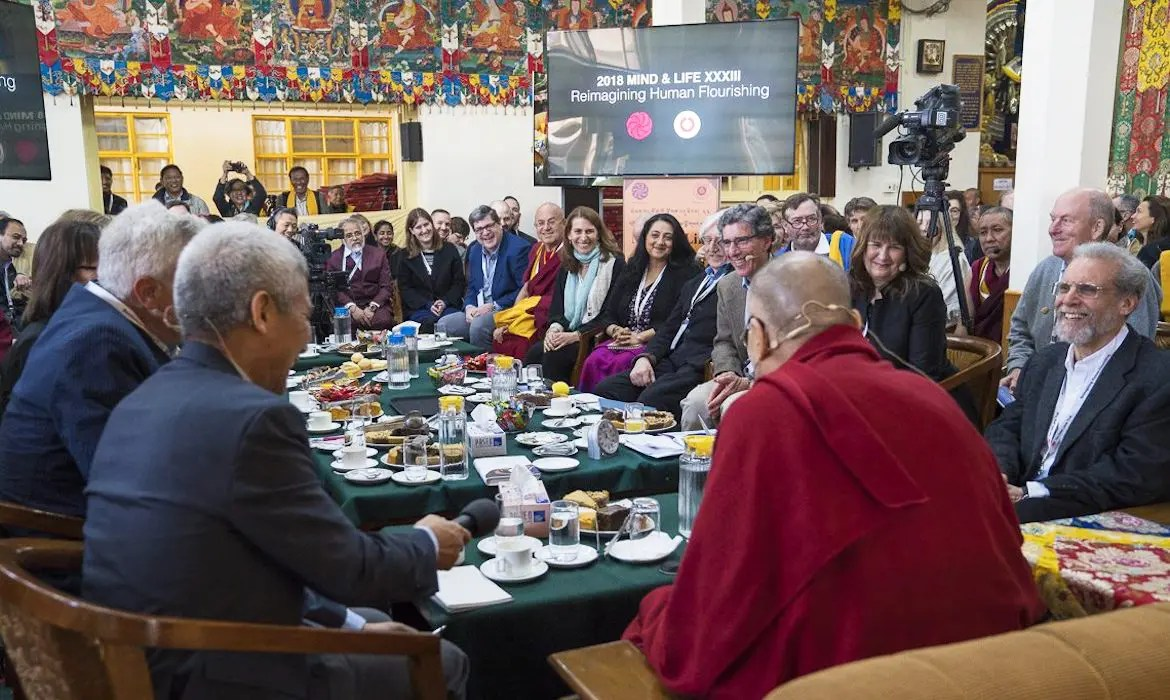 An image shows the 2018 Mind and Life Dialogue taking place in the Main Tibetan Temple in Dharamsala, India. The summit took place from March 12th-16th and focused on the theme of reimagining human flourishing.