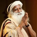 An image shows the great Hindu mystic and guru Jaggi Vasudev, also commonly known as Sadhguru, smiling with his hands together in a customary Indian greeting position.