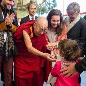 An image shows His Holiness the 14th Dalai Lama greeting a young visitor at the 2018 Mind and Life Dialogue.