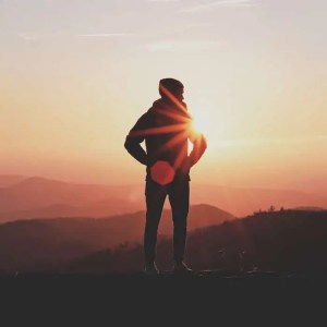 An image shows the silhouette of a man hiking and overlooking picturesque hills as the sun shines down on him. This image represents the idea that we need to transform our minds to achieve life's ultimate aim of finding enjoyment in the days.