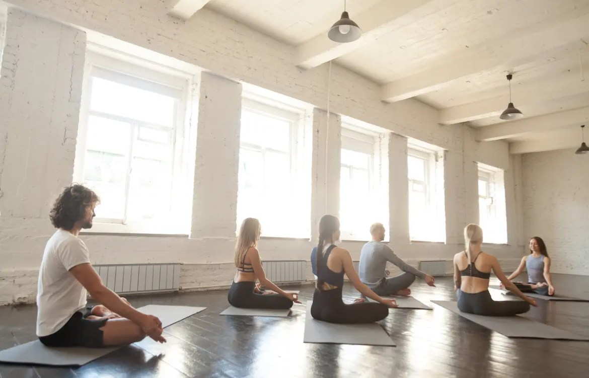 An image shows a group of adults practicing meditation in a sun filled room. This picture serves as a the featured image for Balanced Achievement's article on Mindfulness Based Stress Reduction (MBSR).