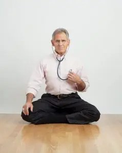An image shows the creator of Mindfulness-Based Stress Reduction, Jon Kabat-Zinn, sitting on the ground in a meditation posture with a stethoscope in his ears and place on his heart.