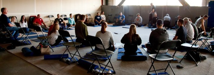 An image shows a group of around 20 individuals sitting in a circle during a Mindfulness-Based Stress Reduction (MBSR) course.