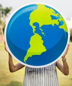 An image shows a woman holding up a large print cutout of a colorful earth. This picture represents the idea that we can change the world with integrity and intelligent effort