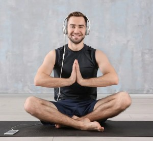 An image shows a young man sitting in lotus position with his head phones, which are plugged into his phone, around his ears. This picture is used in Balanced Achievement's article on the best meditation apps.