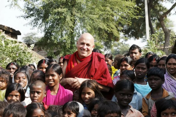 The famed Buddhist monk Matthieu Richard is shown surrounded by a large group of Indian children with a big smile on his face.