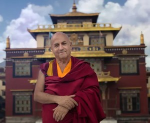 An image shows the iconic Buddhist monk Matthieu Ricard standing in front of the Shechen Monastery in Nepal.
