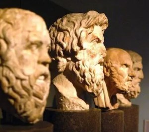 An image shows 4 statues of famous philosophers on display at Rome's Hall of Philosophers.