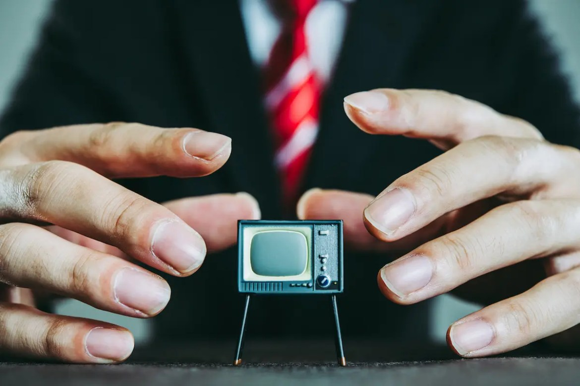 An image shows the hands of a politician hovering over a miniature sized T.V.. This picture serves as the featured image for Balanced Achievement's article titled The Psychology of Political Campaign Advertising.