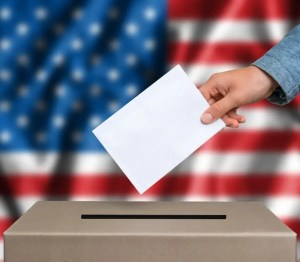 An image shows a man's hand as he's about to drop his voting ballot into a box with an American flag in the backdrop. This image is used in Balanced Achievement's article on the psychology of political campaign advertising.