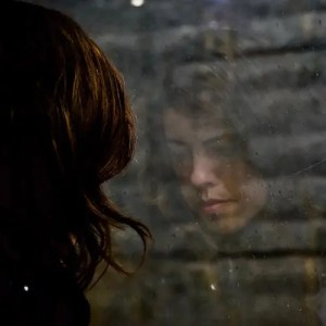 An image shows a young woman, looking into a window where you can see her reflection, in a state of discontentment. This picture represents the ideas of fleeting feelings of pleasure and illusions of fulfillment in Balanced Achievement's article on natural selection and life-satisfaction.