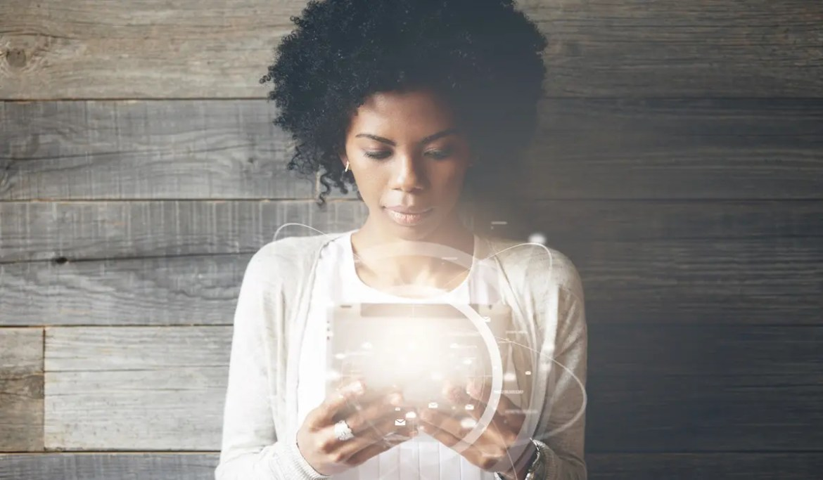 A young and stylish African American woman is sitting against a wooden backdrop as she looks at her tablet which is visually enhanced to look as if it's super powerful. This image serves as the featured image for Balanced Achievement's article title '10 Life-Transforming Personal Development Apps'.