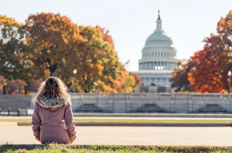 An image shows a young woman stoically sitting and looking at the United States Congressional Capitol from afar. This picture serves as the featured image for Part I of Balanced Achievement's article '6 Spiritual Teachers on America's Divisive Political Climate'.