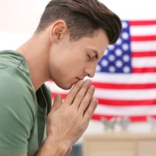 An image shows a young man with his hands together in a prayer position commonly seen in the eastern world. This picture is featured in Part I of Balanced Achievement's article '6 Spiritual Teachers on America's Divisive Political Climate'.