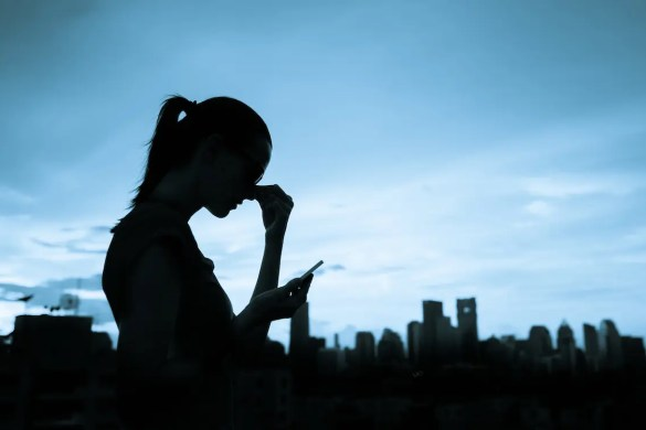 A photo shows the silhouette of a woman with her hand on her nose in a state of despair, as she looks at her smartphone. A city skyline is visible in the background but the photo as dark tone. This picture is used as the featured image of Balanced Achievement's article '3 of the best depression apps to overcome despair .