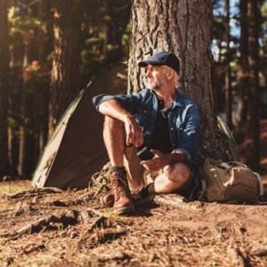 A man sat outside a tent camping in the woods