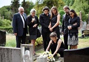 A family grieving at a grave side