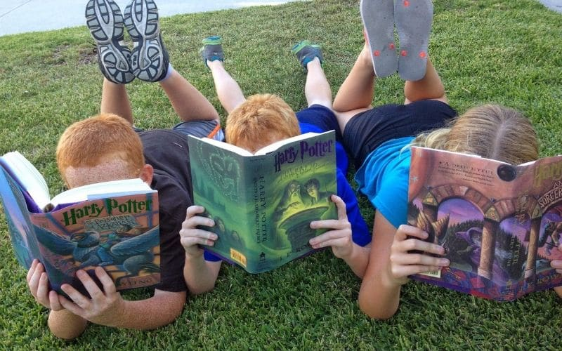 3 kids reading Harry Potter books