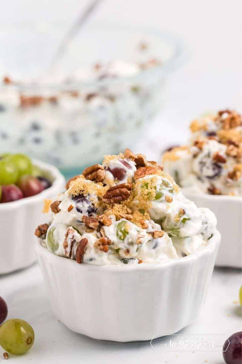 bowls of grape salad with nuts on top