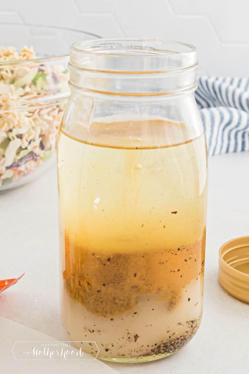 mason jar with dressing ingredients layered inside