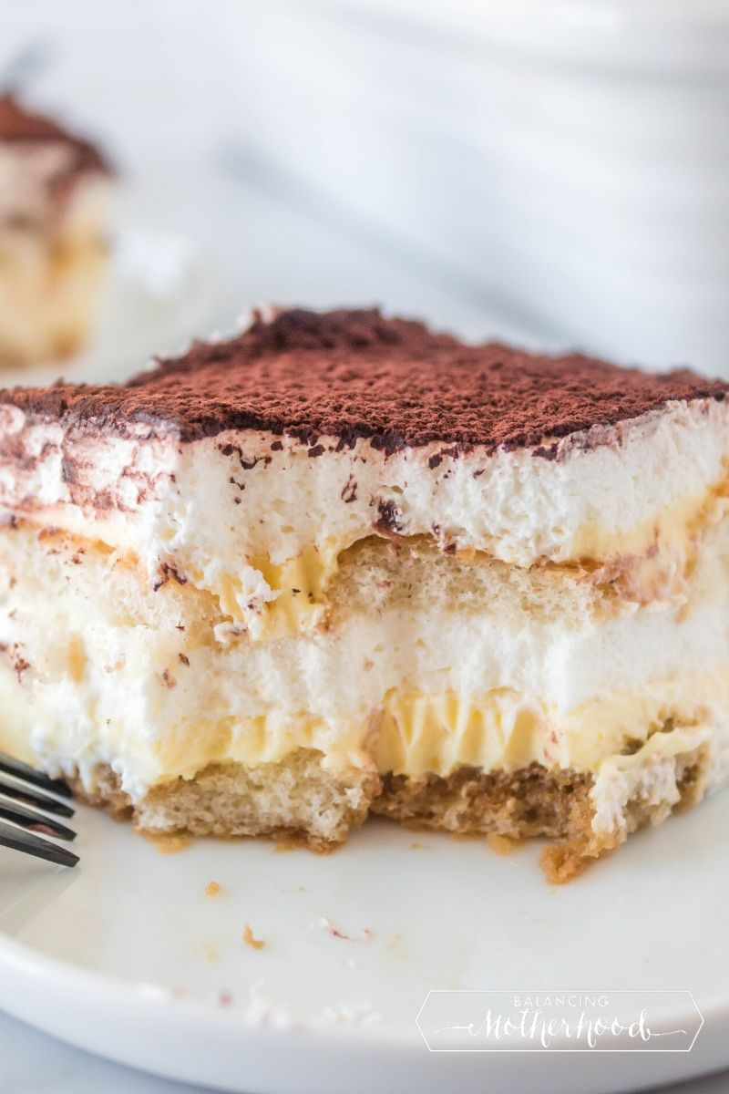 slice of tiramisu on plate with bite out of it